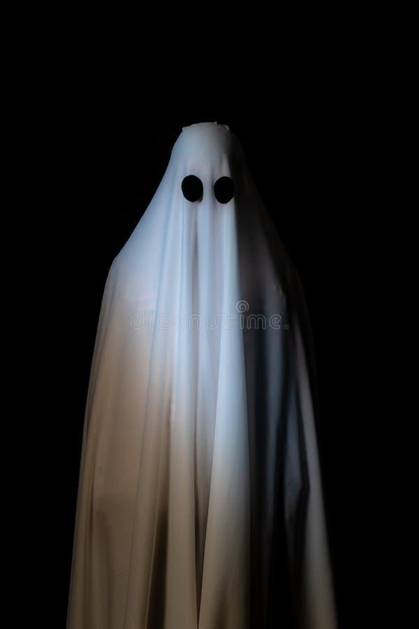 Alguém coberto com o pano branco com olhos roxos grandes em vagabundos pretos fotos de stock