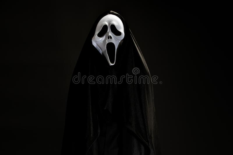 Alguém na tampa preta com a máscara branca do fantasma cosplay à C.A. do diabo foto de stock royalty free