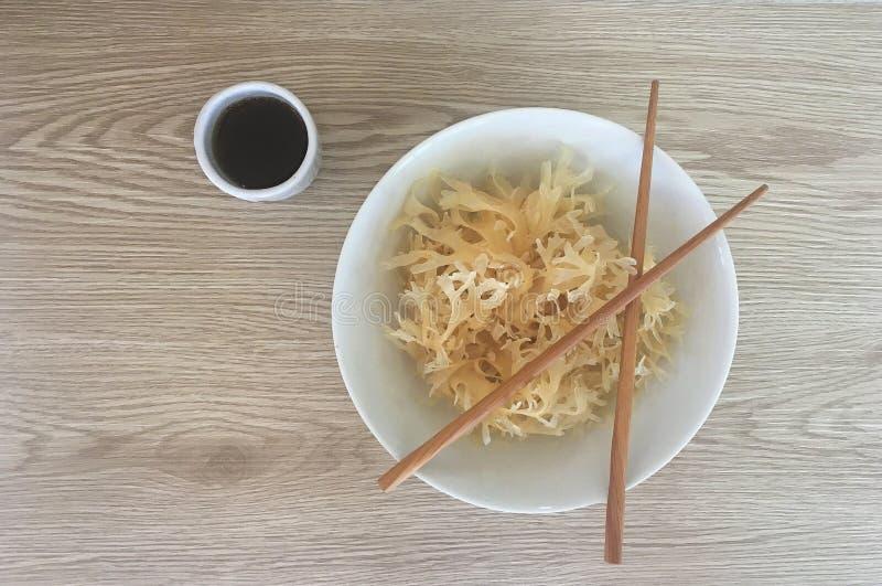 Algue et sauce d'accompagnement asiatique avec des baguettes photos libres de droits