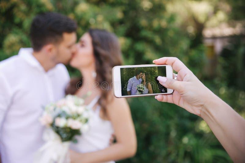 Alguien está tomando una imagen en la novia y el novio del teléfono mientras que se besan Pares hermosos en blanco imagenes de archivo