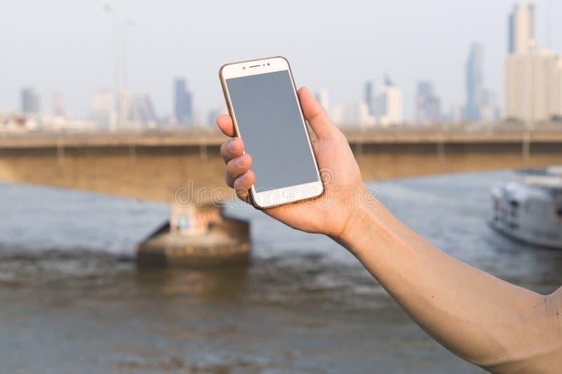 Alguien que sostiene su smartphone para conseguir la buena señal en el puente fotografía de archivo