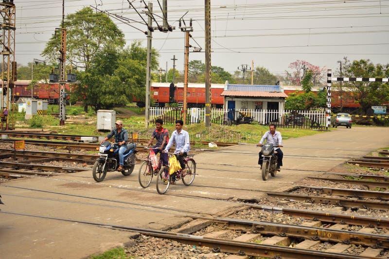 Algum pessoa cruza um cruzamento de estrada de ferro na motocicleta ou no ciclo perto da estação de trilho de Tatanagar fotografia de stock royalty free