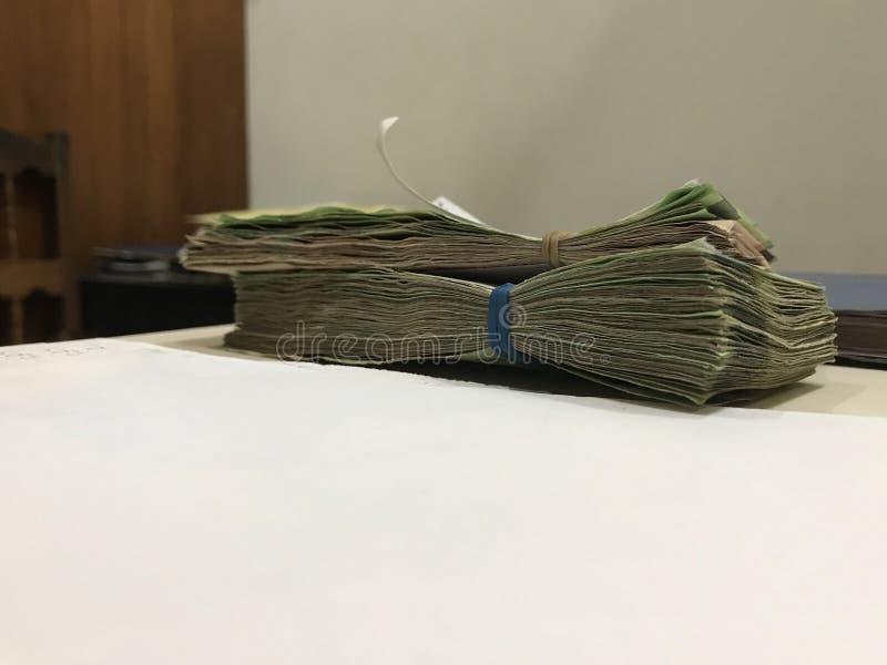 Algumas contas de dinheiro do peso mexicano empilhadas em uma tabela colorida bege fotografia de stock royalty free