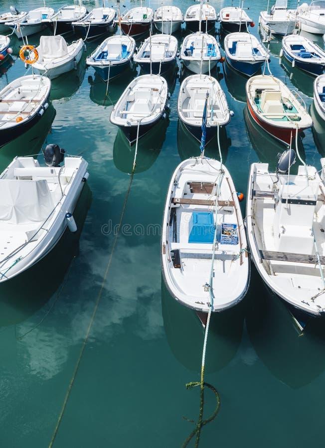 Algumas cores brilhantes do barco no lago da água azul do fundo do cais, a pesca e o esporte de barco na paisagem do verão, o cur imagens de stock