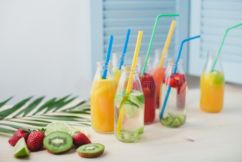 Algumas garrafas de vidro na tabela com coctails diferentes do fruto fotografia de stock