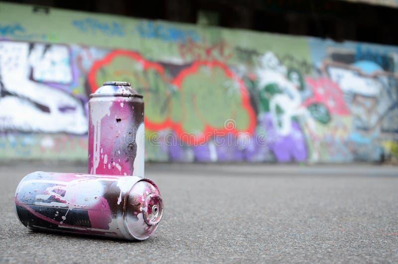 Algumas latas de pulverizador usadas com mentira cor-de-rosa e branca da pintura no aspha foto de stock royalty free