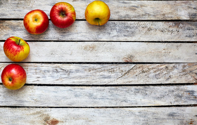 Algumas maçãs vermelhas e amarelas na tabela de madeira branca imagens de stock