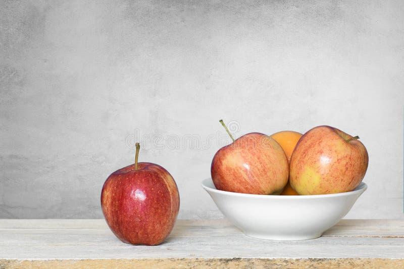 Algumas maçãs vermelhas em uma prateleira de madeira branca e em uma bacia contra um fundo branco espa?o vazio da c?pia fotografia de stock royalty free