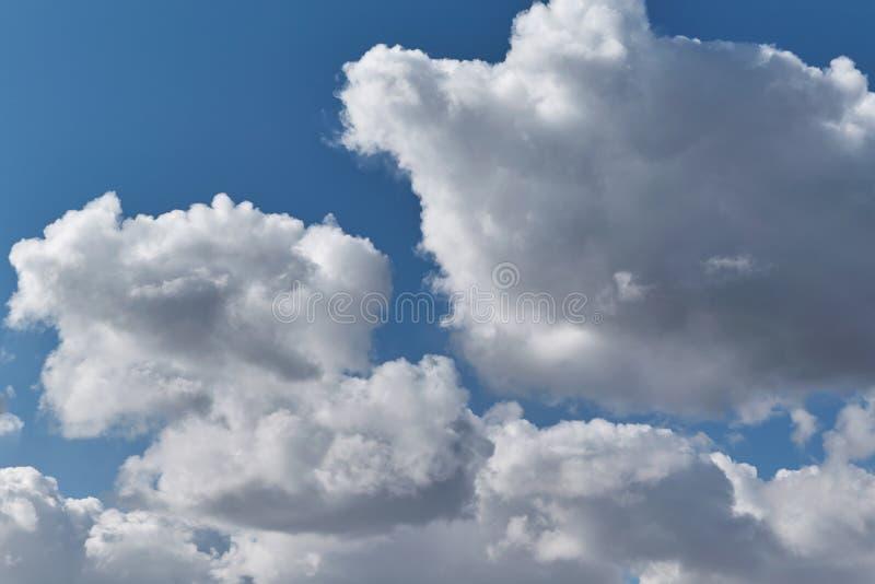 Algumas nuvens de cúmulo grandes em um céu azul claro imagem de stock royalty free
