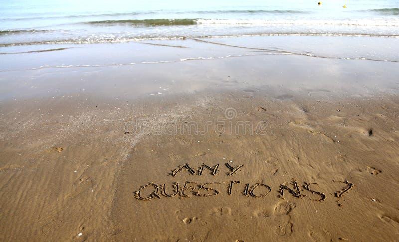 Algumas perguntas que escrevem na areia da praia fotografia de stock