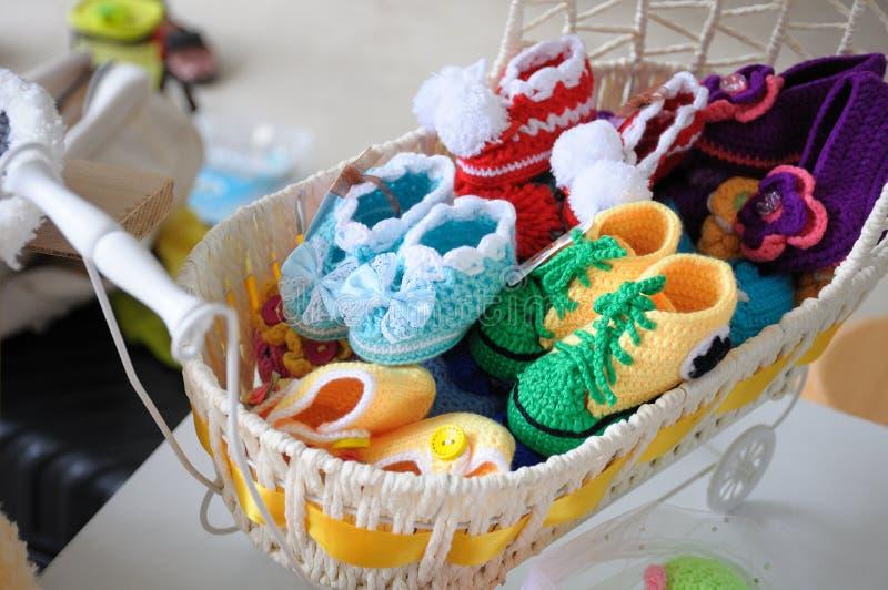 Algumas sapatas de bebês feitas malha coloridas fotografia de stock