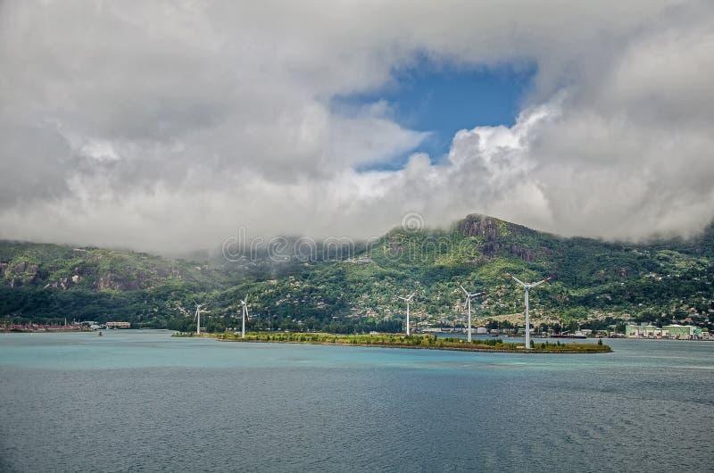 Algumas turbinas eólicas na ilha com montes verdes e as nuvens grandes fotos de stock