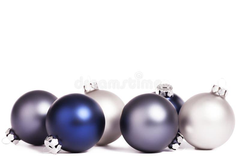 Alguna plata y bolas azules de la Navidad foto de archivo