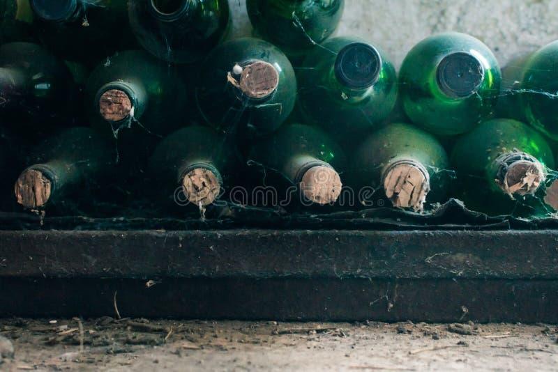 Algunas botellas de vino muy viejas y polvorientas en una bodega foto de archivo libre de regalías