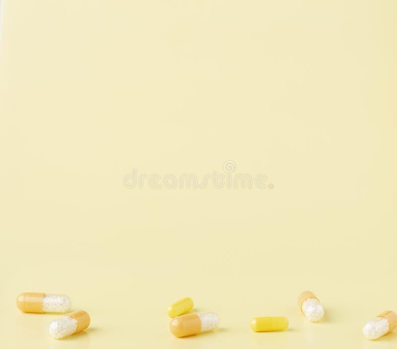 Algunas cápsulas blanco-amarillas de la droga en el fondo amarillo imagen de archivo