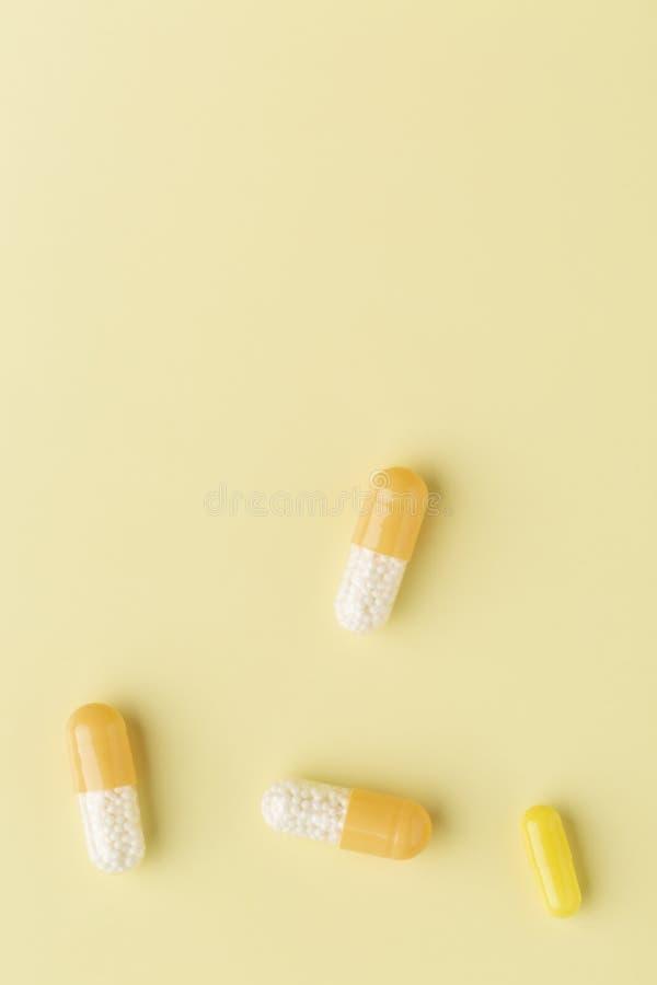 Algunas cápsulas blanco-amarillas de la droga en el fondo amarillo foto de archivo