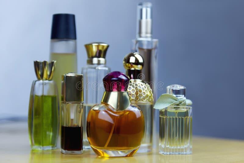 Algunas filas de las botellas de perfume en la tabla de madera Perfumes viejos del vintage imagen de archivo libre de regalías