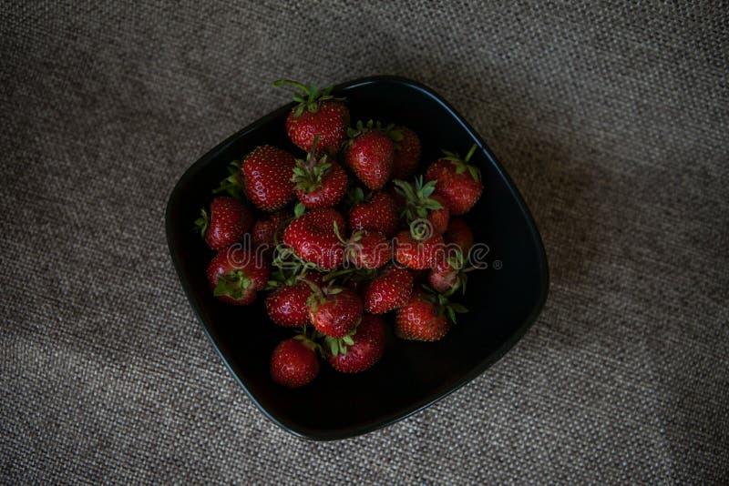 Algunas fresas en una placa negra fotos de archivo libres de regalías