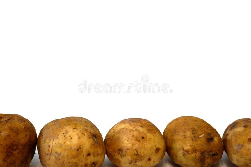 Algunas patatas marrones en el cierre blanco del fondo para arriba imagen de archivo libre de regalías