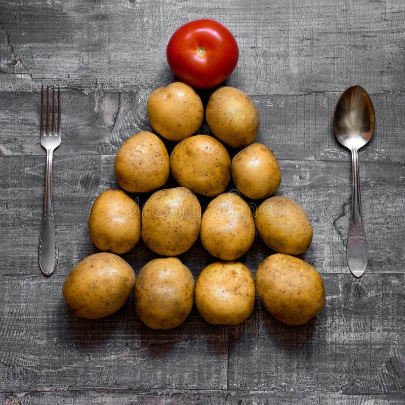 Algunas patatas y un tomate en una vieja tabla o superficie de madera se presenta en la forma de un árbol de navidad Opinión supe fotos de archivo