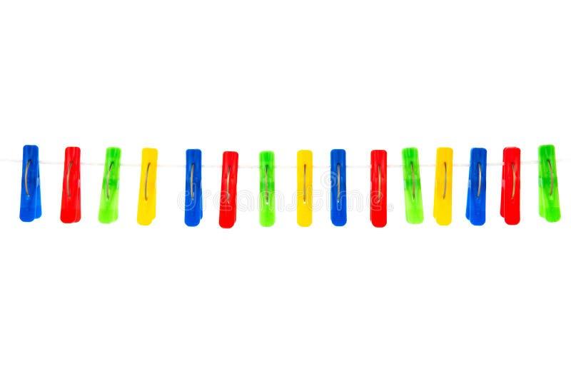 Algunas pinzas coloreadas en un fondo blanco fotos de archivo