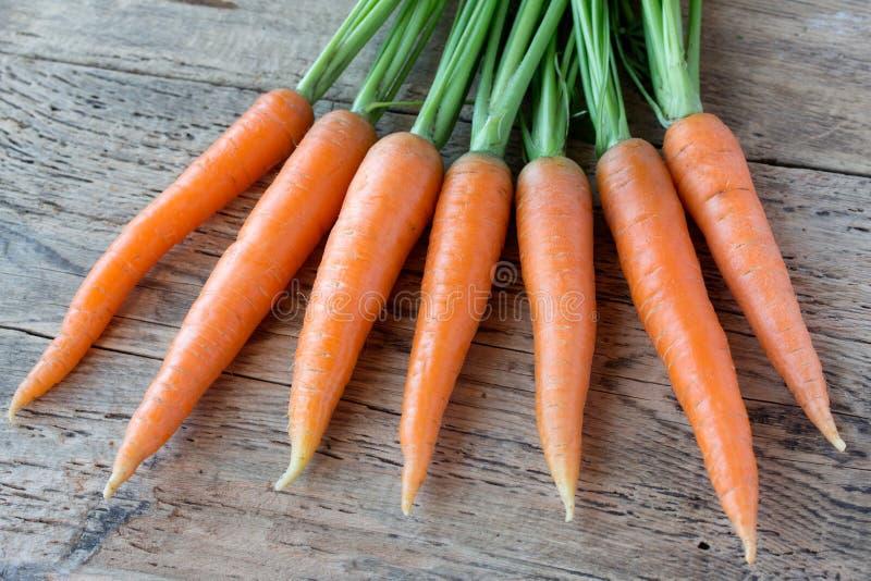 Algunas zanahorias frescas en el escritorio de madera viejo foto de archivo libre de regalías