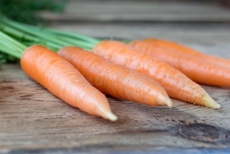 Algunas zanahorias frescas en el escritorio de madera viejo fotos de archivo libres de regalías