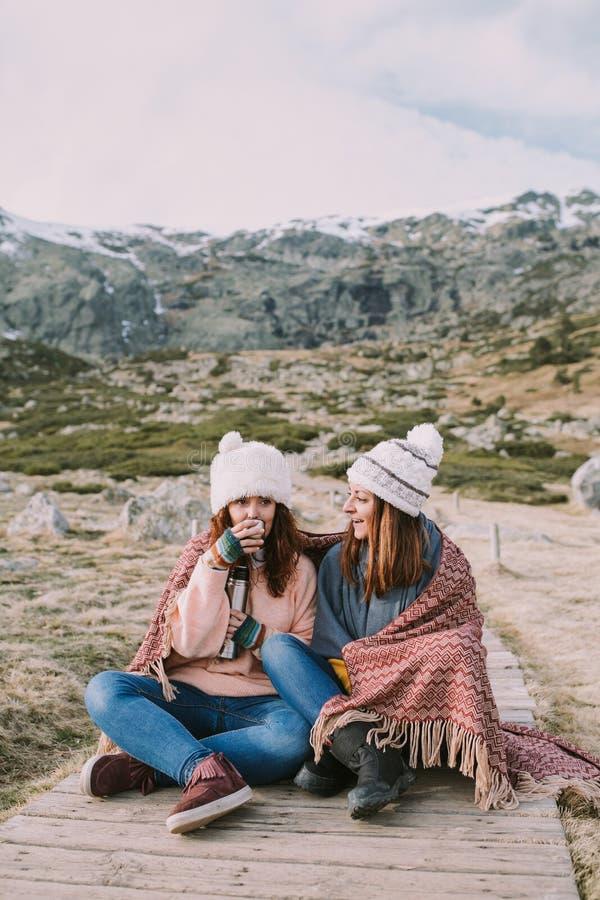 Algunos amigos gozan de la montaña mientras que se están sentando tomando un caldo fotos de archivo