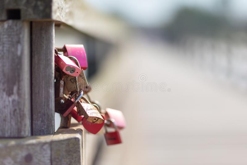 Algunos candados grabados que cuelgan en un puente como símbolo para los amantes foto de archivo
