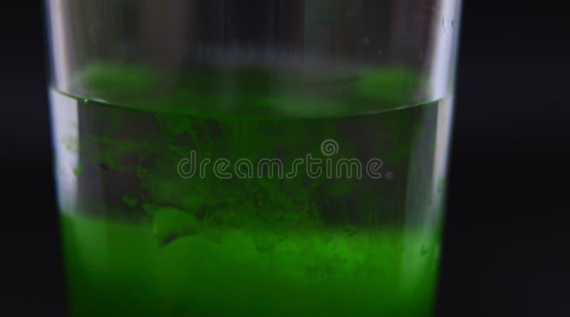Algunos descensos del veneno verde en un vidrio que se está mezclando para arriba con agua imagen de archivo libre de regalías