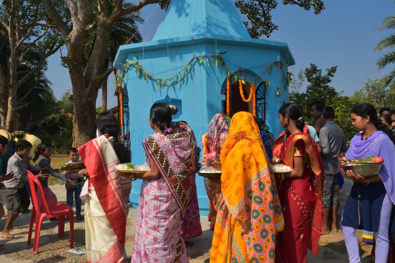 Algunos hombres y mujeres que realizan rituales del puja caminando alrededor del templo y que distribuyen los dulces a los niños fotos de archivo libres de regalías