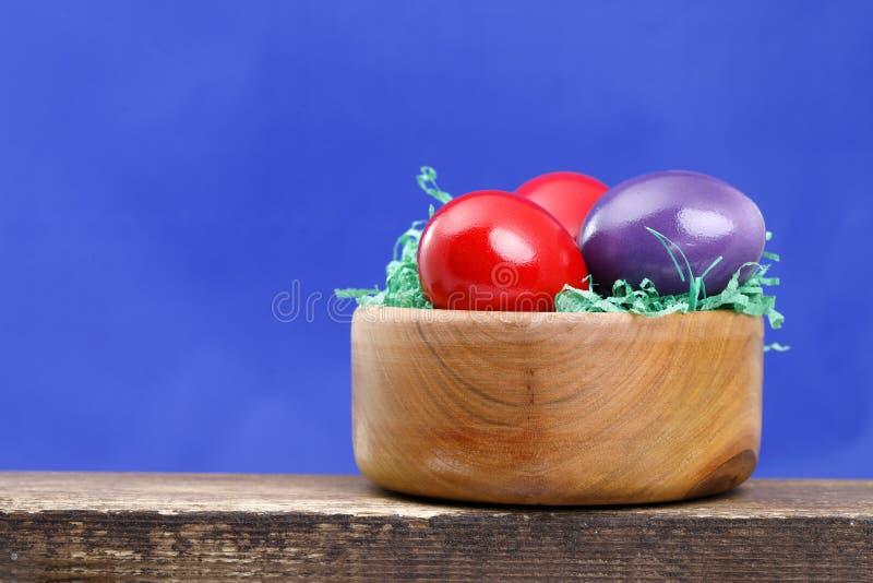 Algunos huevos de Pascua en un cuenco de madera en un tablero, fondo azul imagen de archivo