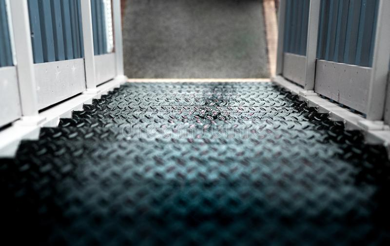 Algunos pasos mojados peligrosos del metal con una verja de madera blanca fotos de archivo