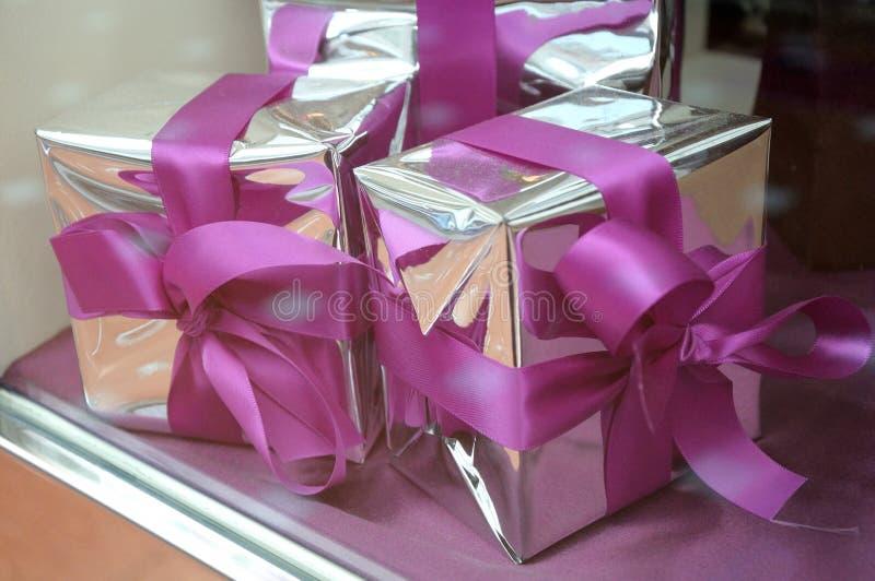 Algunos presentes envueltos con los arcos reflexivos del papel de plata y del rosa fotografía de archivo