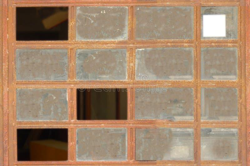 Algunos vidrios rotos en ventana marrón del metal fotografía de archivo libre de regalías
