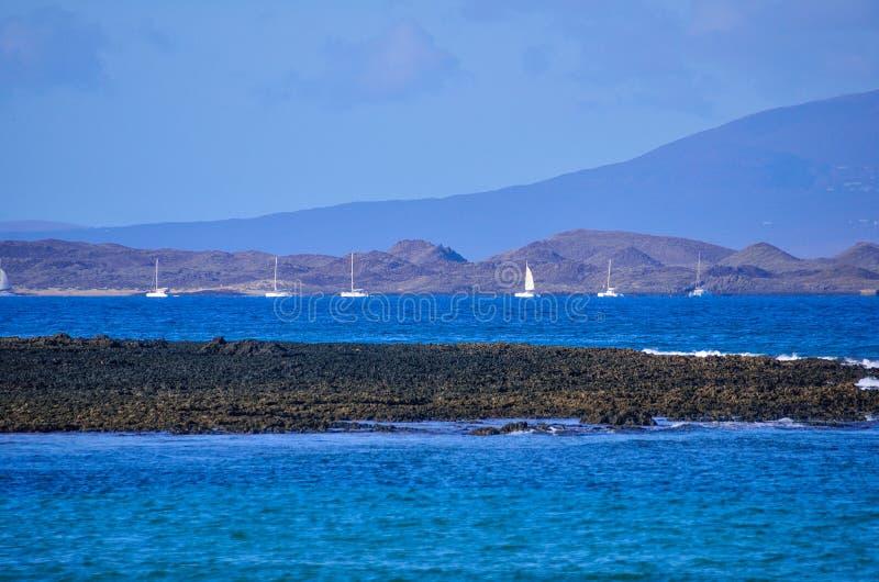algunos yates permanecen en el océano cerca de la isla foto de archivo