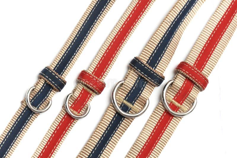 Alguns azul e vermelho costuraram curvaturas de correias e laços de tamanhos diferentes fotografia de stock royalty free