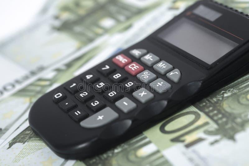 Alguns euro e uma calculadora na tabela, na finança e nas economias Conceito do neg?cio foto de stock