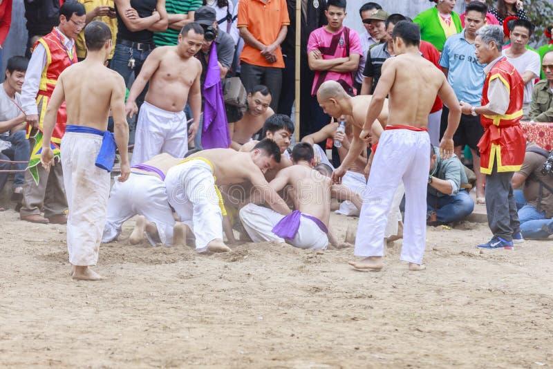 Alguns homens novos jogam com a bola de madeira no ano novo lunar do festival em Hanoi, Vietname o 27 de janeiro de 2016 foto de stock royalty free