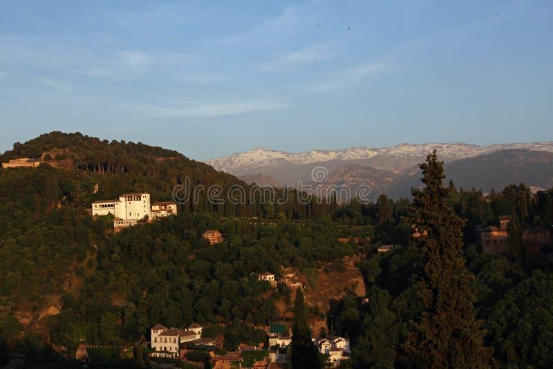 Alhambra durante puesta del sol con Sierra Nevada Mountains en el fondo, Granada, España fotografía de archivo
