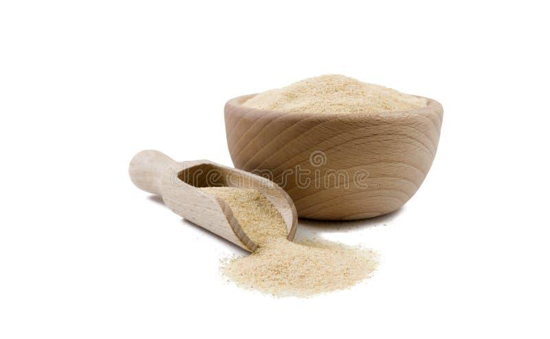 Alho à terra moído secado na bacia de madeira e na colher isoladas no fundo branco Especiarias e ingredientes de alimento fotografia de stock