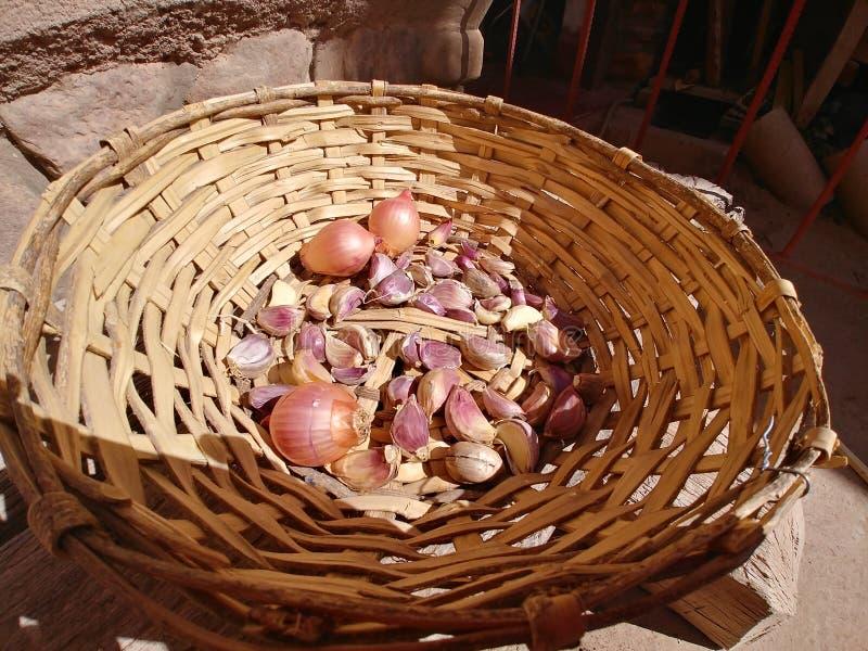 alho e cebolas em uma cesta fotos de stock