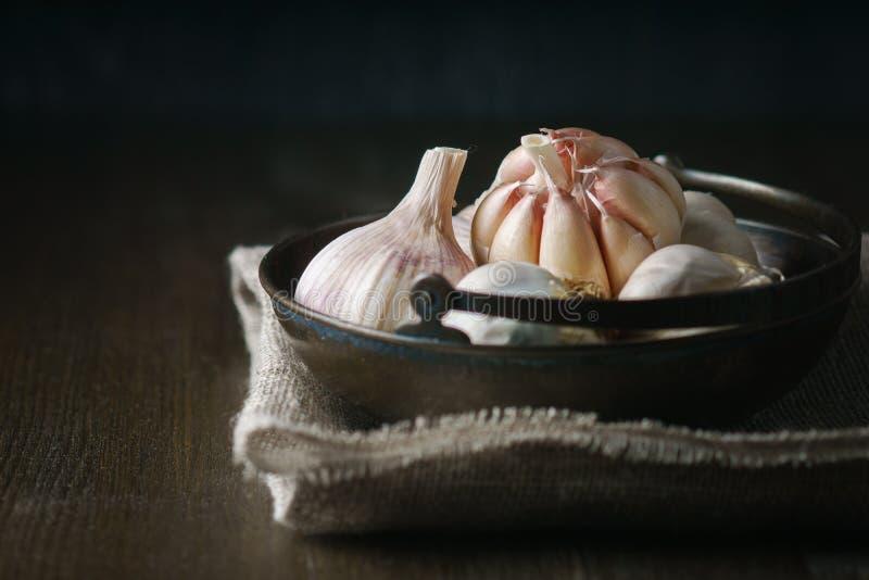 Alho e cravos-da-índia de alho na obscuridade imagens de stock