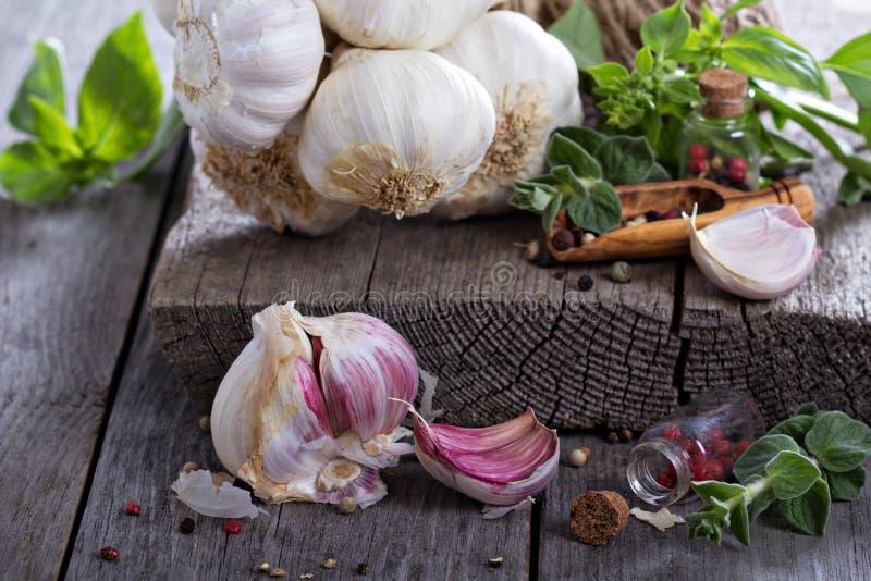Alho, especiarias e folhas frescos da salada na tabela imagens de stock royalty free