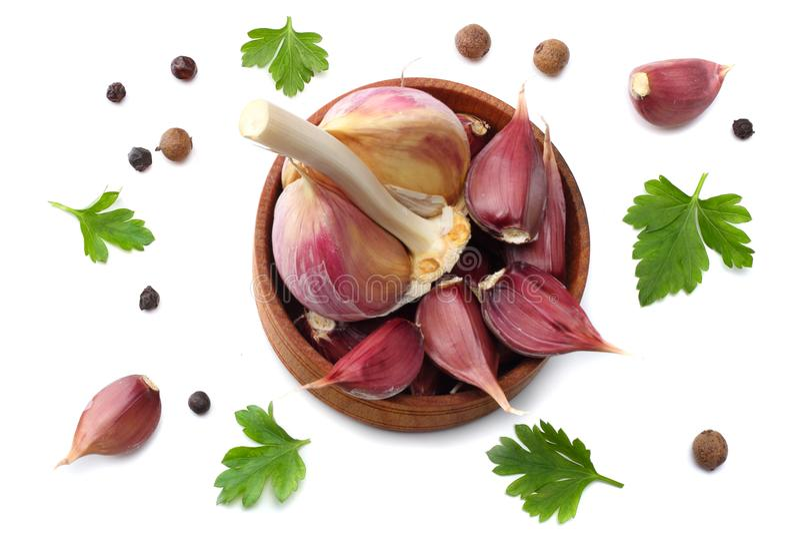 Alho na bacia, na salsa de madeira e nas especiarias isoladas no fundo branco Vista superior fotografia de stock royalty free