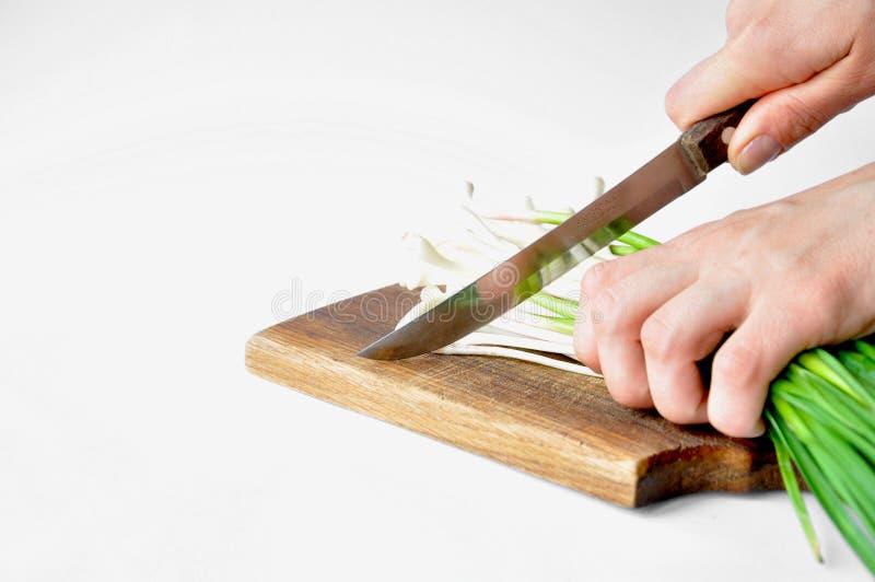 Alho verde fresco na placa com uma faca foto de stock