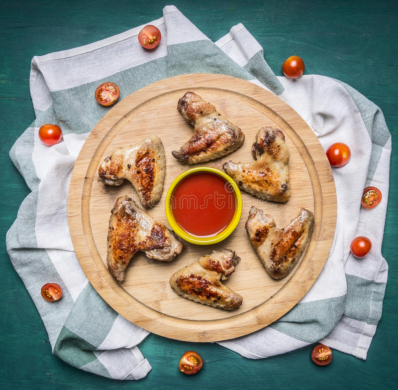 Ali di pollo arrostite con il tagliere piccante della salsa di peperoncino rosso sui pomodori ciliegia a strisce di un tovagliolo fotografie stock libere da diritti