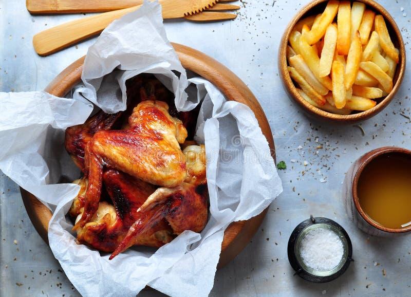 Ali di pollo arrostite con le patate fritte in una ciotola di legno sui precedenti di alluminio immagini stock