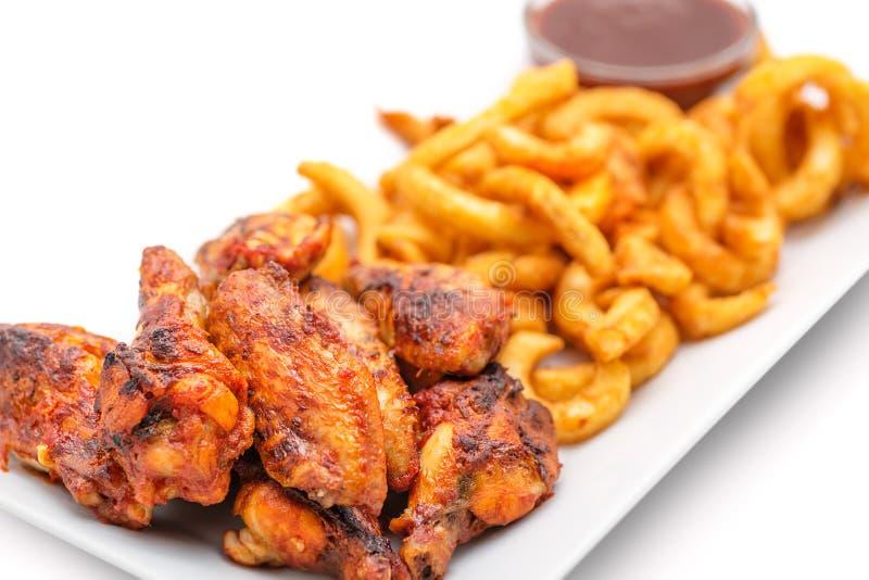Ali di pollo arrostite con le patate fritte una salsa al pomodoro sul piatto bianco fotografie stock libere da diritti