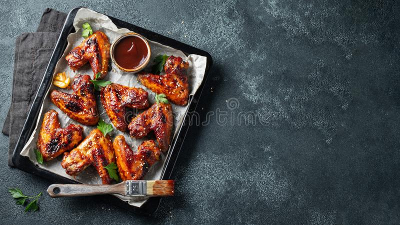 Ali di pollo arrostito in salsa barbecue con i semi di sesamo ed il prezzemolo in un vassoio bollente su una tavola scura Vista s immagini stock libere da diritti